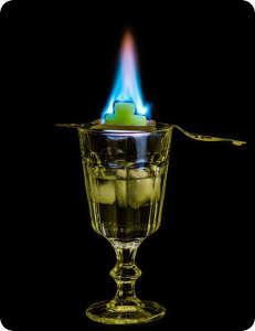 Absinth trinken, Absinthlöffel mit brennendem Zucker, Feuerritual